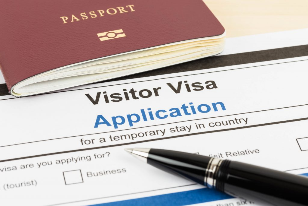Visa application form with passport and pen